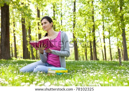 student girl sitting  on grass and holding book - stock photo