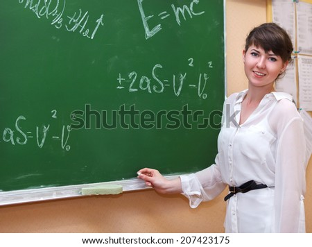 Student girl standing near blackboard in the classroom - stock photo