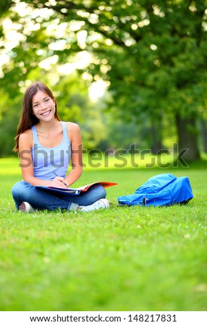 Student girl studying in park going back to school at university college. Happy student sitting studying, writing and reading outside. Multi ethnic Chinese Asian / Caucasian female student woman - stock photo