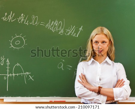 Student girl wearing glasses standing near blackboard in the classroom - stock photo