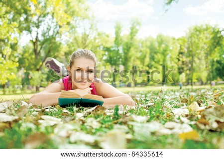 student girl with book lying on grass in park - stock photo