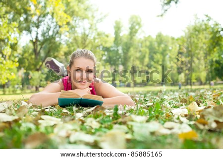 student girl with book lying on grass in park
