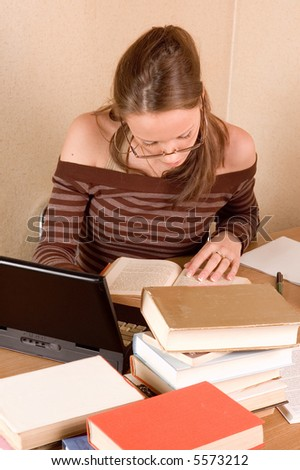 Student girl with books and laptop in her room - stock photo