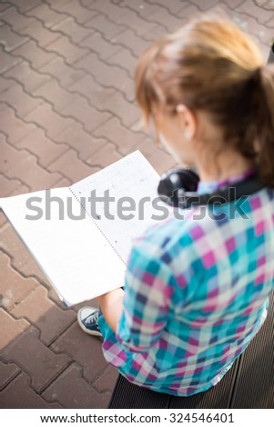 Student girl with copybook on bench outdoor. Summer campus park. Studying to exam. - stock photo