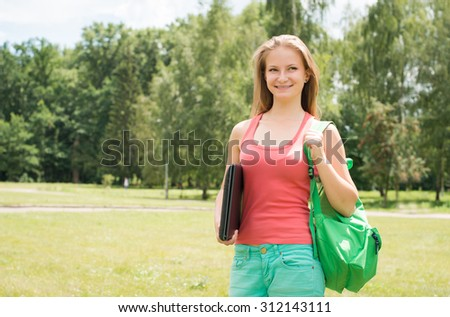 Student girl with laptop and  school bag outdoors. College or university student young woman in summer park smiling happy.