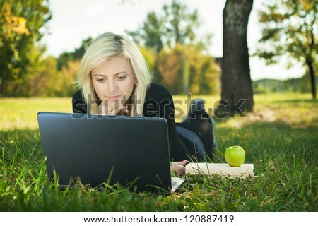 student girl with laptop studying in park - stock photo