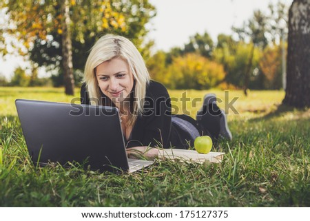 student girl with laptop studying in the park - stock photo