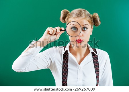 Student girl with loupe in front of blackboard - stock photo