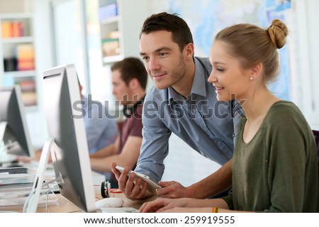 Student girl with trainer working on computer and tablet - stock photo