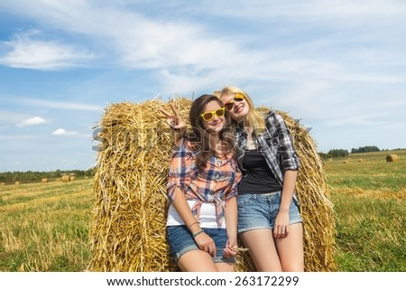 Student girls in checkered shirts and denim hot pants are resting on large round straw bale at big farm harvested cereal field background and navy blue sky. Young girls in sunglasses and show V sign - stock photo