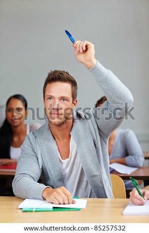 Student giving answer in class with his hand raised - stock photo