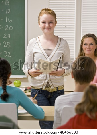 Student giving report in classroom - stock photo