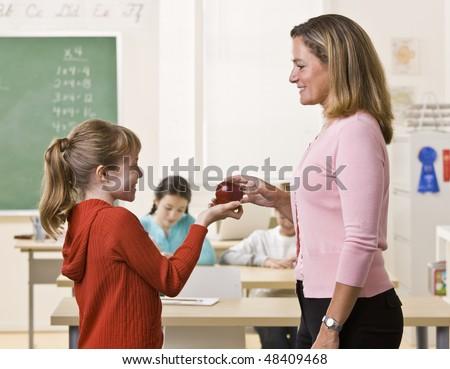 Student giving teacher apple - stock photo