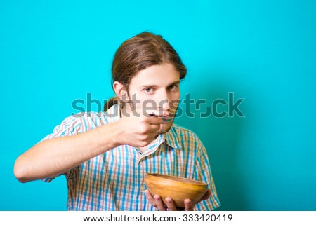 Student guy eating out of pottery fork - stock photo