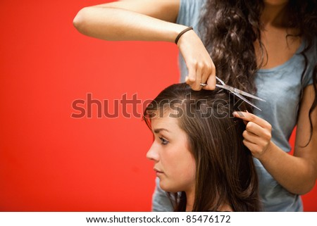 Student hairdresser cutting hair with scissors - stock photo