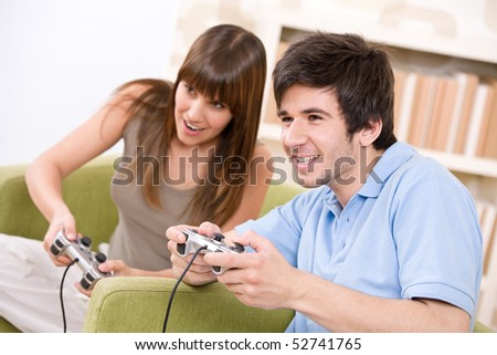 Student - happy teenagers playing video game with control pad in living room - stock photo