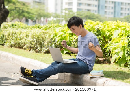 Student having good news on his computer - stock photo