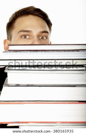 Student hiding behind stack of books