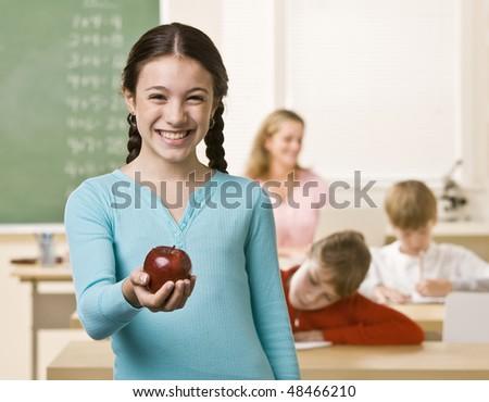 Student holding apple - stock photo