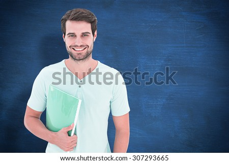 Student holding notepad against blue chalkboard