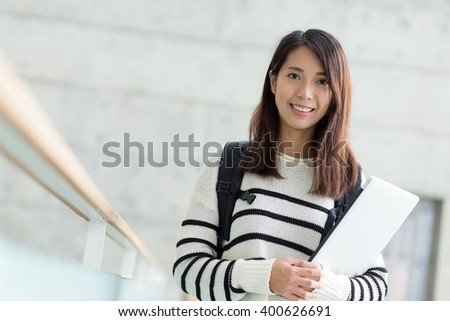 Student holding with lap top computer inside school campus building - stock photo