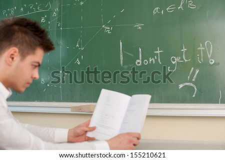 Student in a classroom with a book thinking hard - stock photo