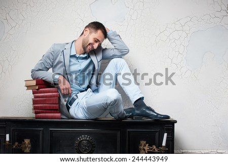 student in a delight from a home work. sits on an upright piano with books, inclining a head downward - stock photo