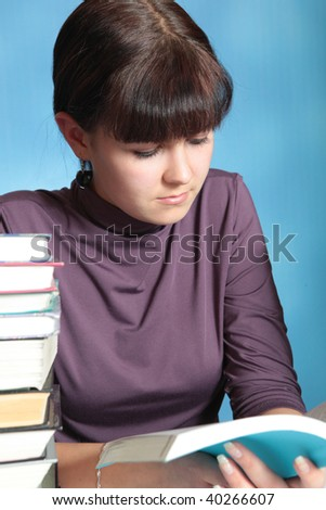 Student in a library surrounded by piles of books - stock photo