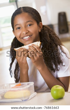Student in cafeteria eating lunch - stock photo