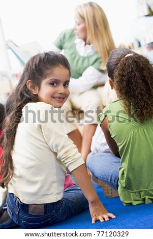 Student in class looking at camera with teacher reading in background (selective focus) - stock photo