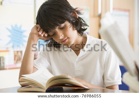 Student in class reading book (selective focus) - stock photo