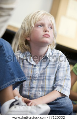 Student in class sitting on floor bored (selective focus) - stock photo