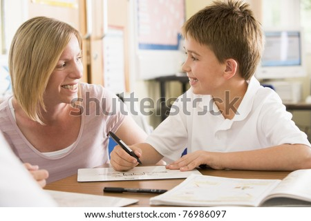 Student in class taking notes with teacher helping - stock photo