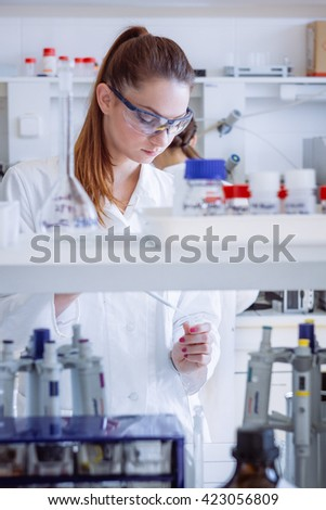 Student in lab. Chemist working with pipette. - stock photo