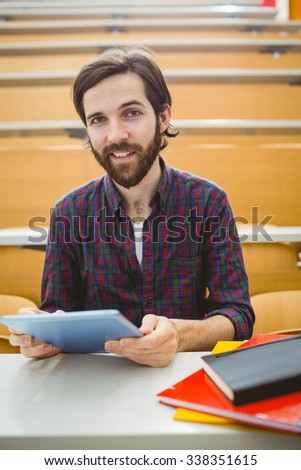 Student in lecture hall using tablet at the university