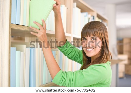 Student in library - happy woman choose book from bookshelf - stock photo