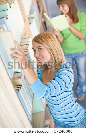 Student in library - two woman choose book in bookshelf - stock photo