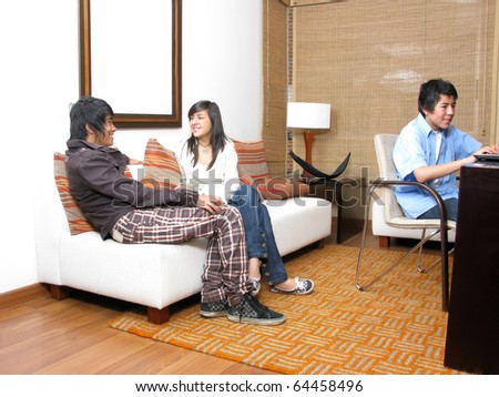 Student in living room with laptop smiling - stock photo
