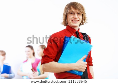 Student in red shirt wearing glasses and with books