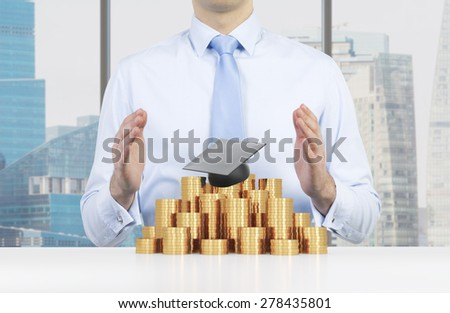 Student is placing his hands over the graduation hat and coins pyramid. A concept of a high price for the university education. New York Background. - stock photo
