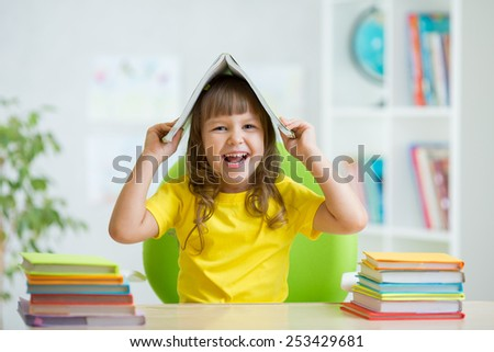 Student kid girl with a book over her head at nursery - stock photo