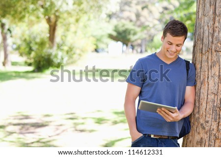 Student leaning against a tree with a touch pad in a park - stock photo