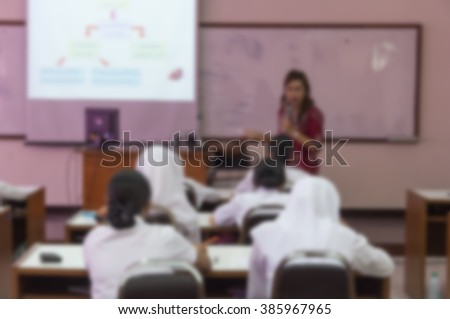 student learning business sitting in classroom with teacher front and white projector slide screen Blur blurred view from back