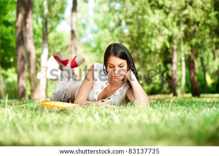 student learning outdoor, student girl relaxing and reading book in park, school education - stock photo