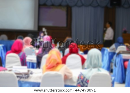 student learning sitting in classroom with teacher front and white projector slide screen Blur blurred view from back abstract