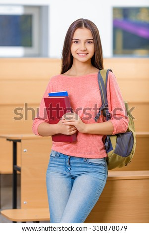 Student life. Appealing young girl is standing in the classroom while holding her textbooks. - stock photo