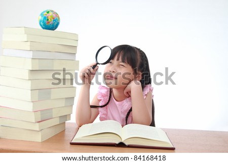 Student little girl reading with magnifying glass look the globe - stock photo