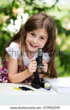 student little girl with microscope - working outside in nature - stock photo