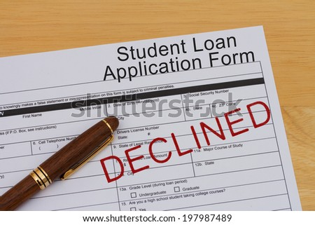 Student Loan Application Form with a pen and declined stamp on a wooden desk