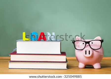 Student loan theme with textbooks and piggy bank and green chalkboard background - stock photo